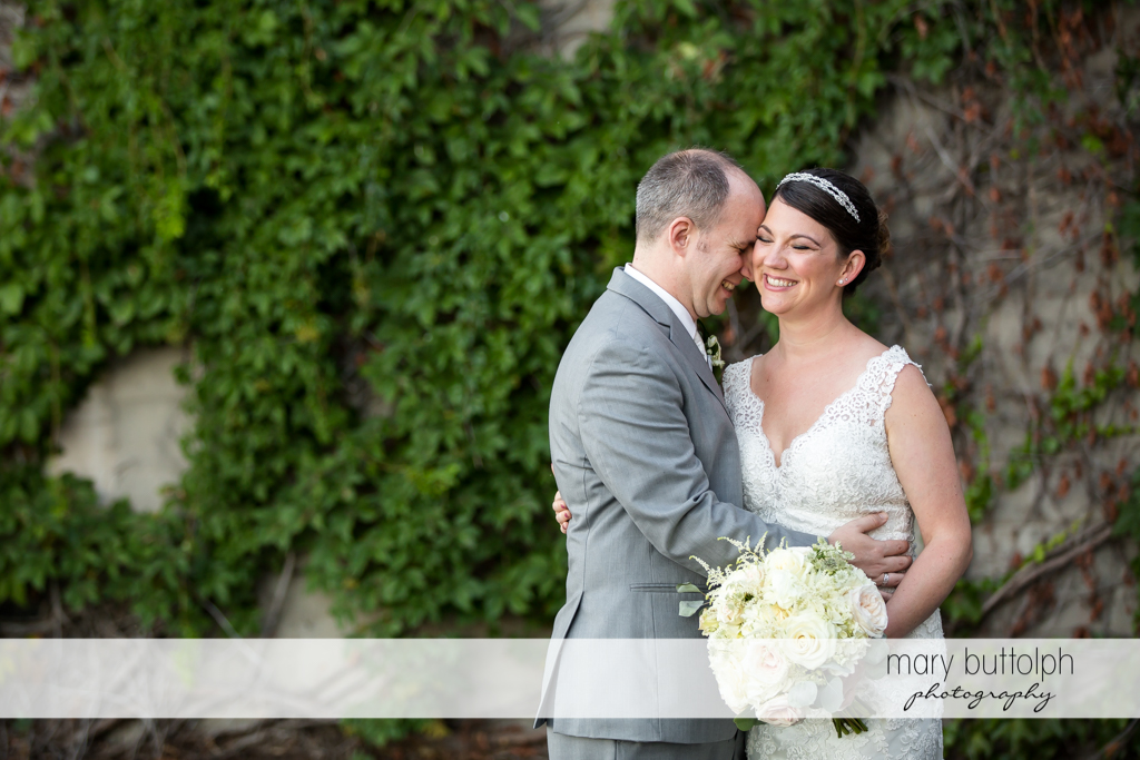 Couple in a good mood in front of a stone wall at The Sherwood Inn Wedding