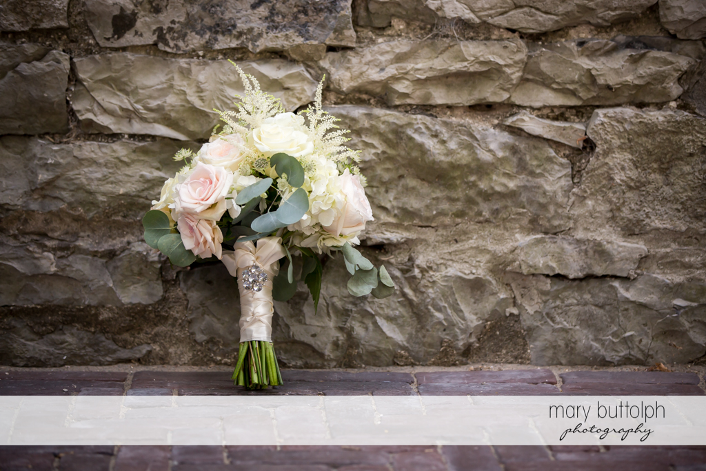 Bouquet rests on a stone wall at The Sherwood Inn Wedding