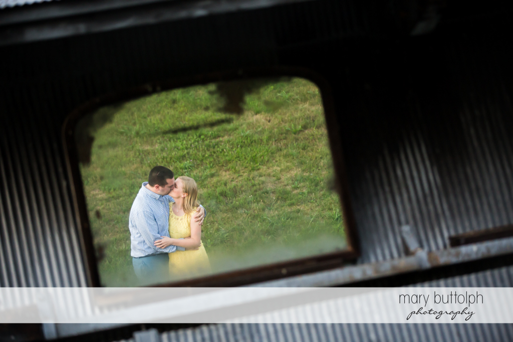 Couple are framed by old window in Syracuse Engagement