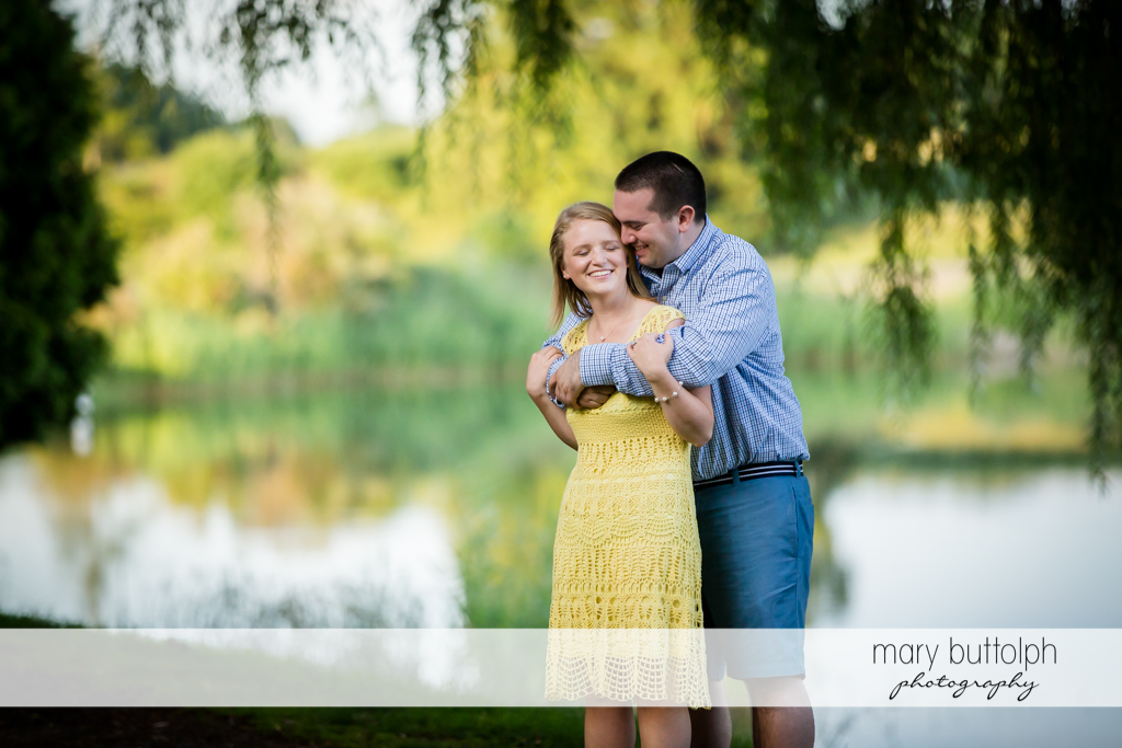 Couple spend precious moments in front of a lake in Syracuse Engagement