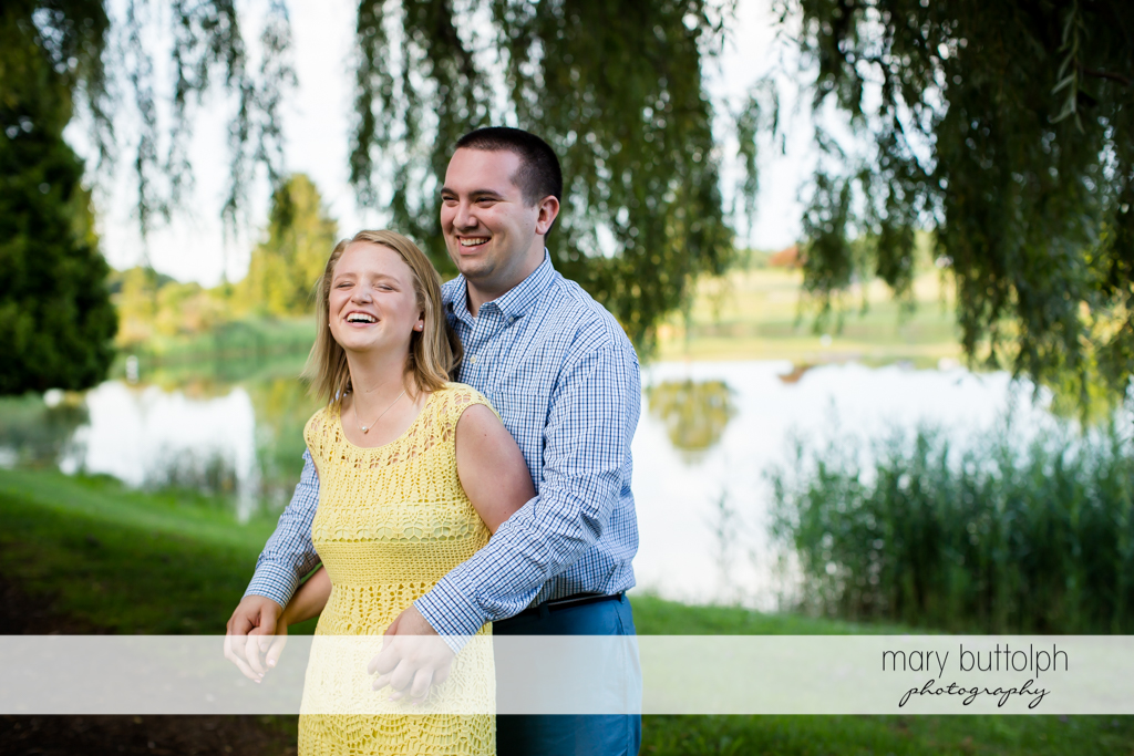 Couple smiling with the calm lake behind them at Syracuse Engagement
