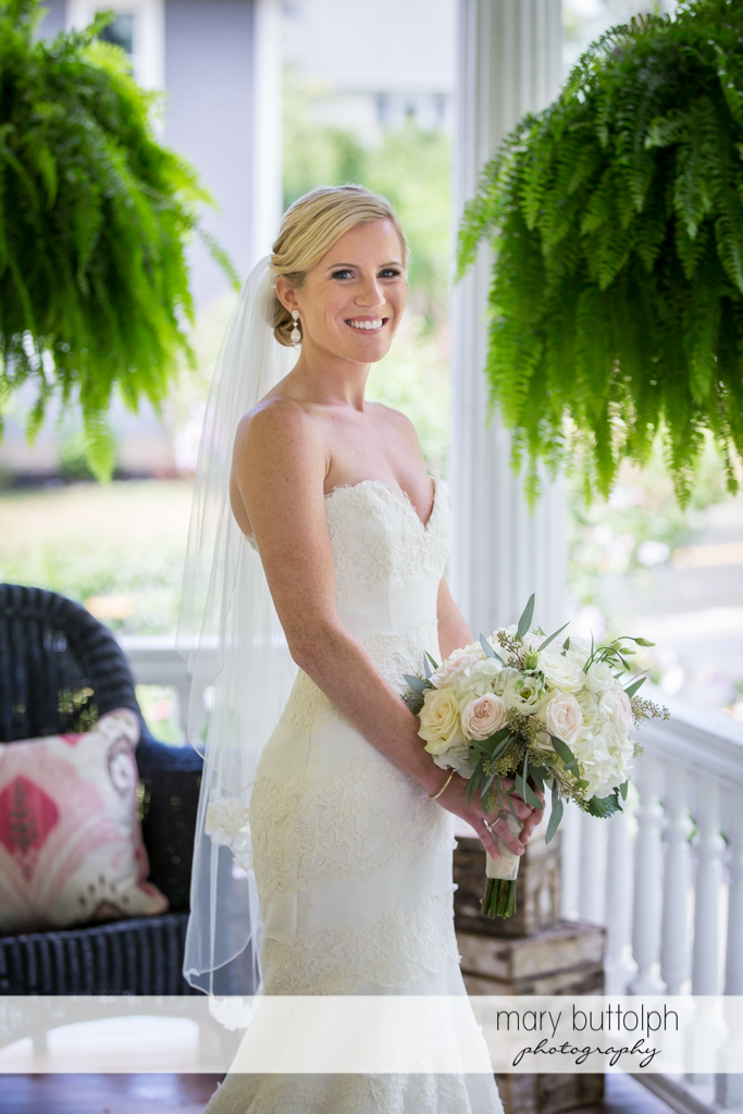 Bride with bouquet stands at the porch at Skaneateles Country Club Wedding
