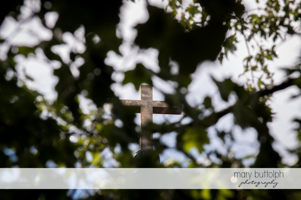 Cross of the church is partly covered by trees at Skaneateles Country Club Wedding