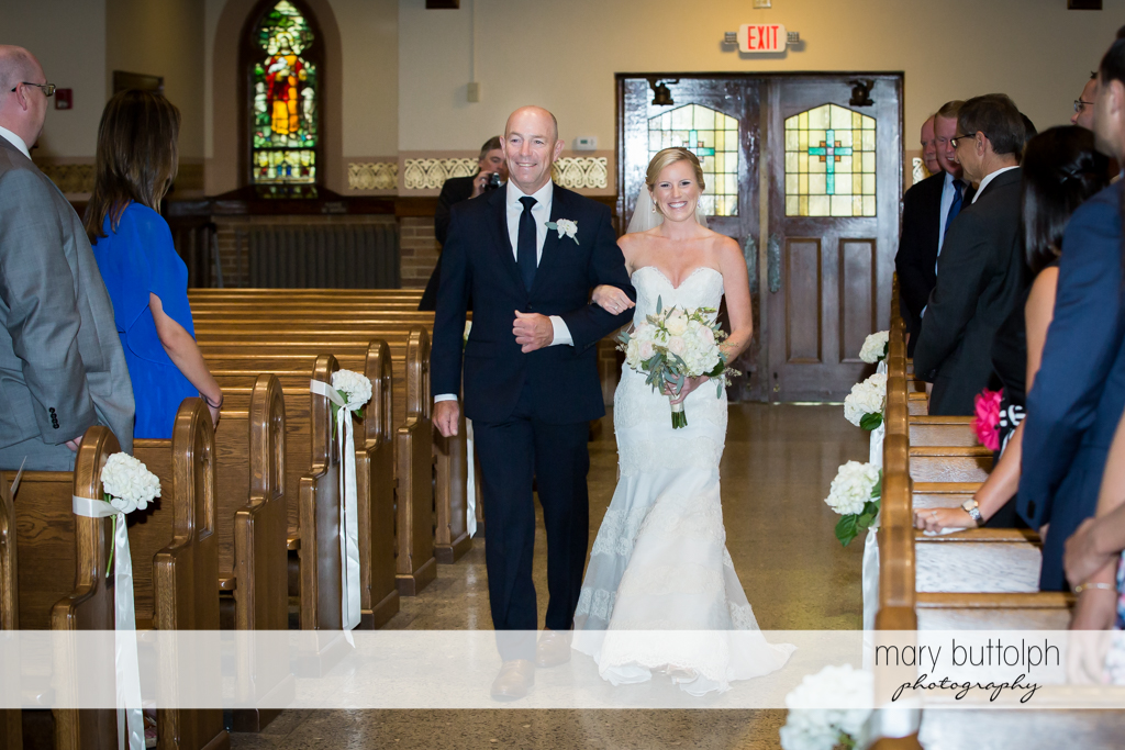 Bride walks down the aisle of the church accompanied by her father at Skaneateles Country Club Wedding
