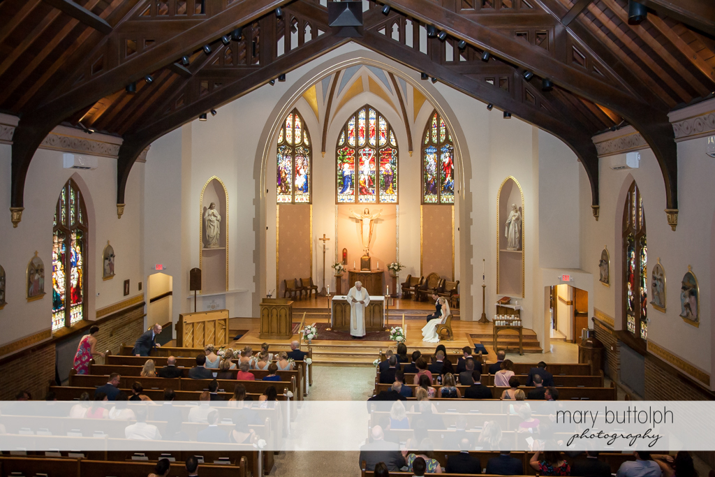 Couple sit in front of the altar as guests look on at Skaneateles Country Club Wedding