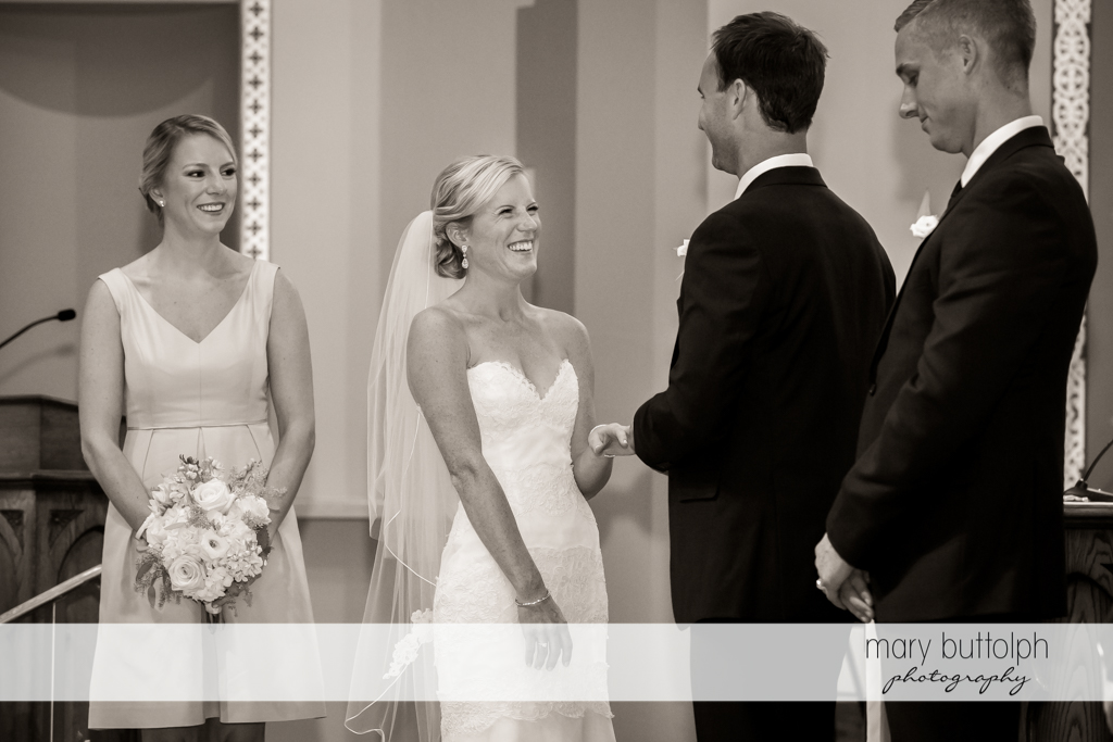 Couple face each other as the bridesmaid and best man look on at Skaneateles Country Club Wedding