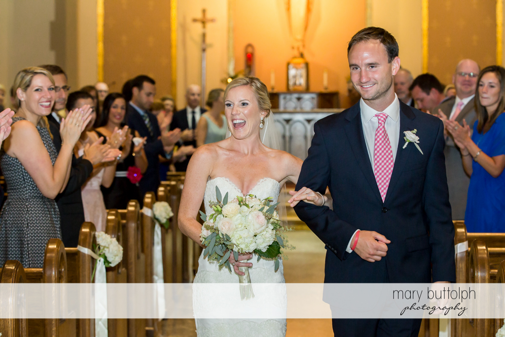 Couple leave church after the wedding as guests applaud them at Skaneateles Country Club Wedding