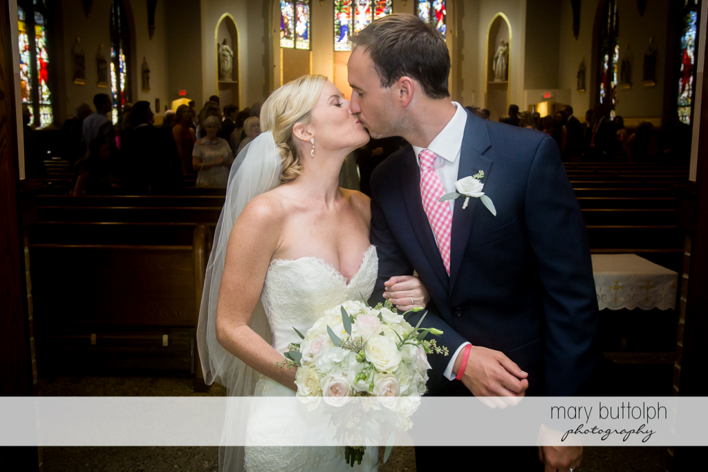 Couple kiss as they exit the church at Skaneateles Country Club Wedding