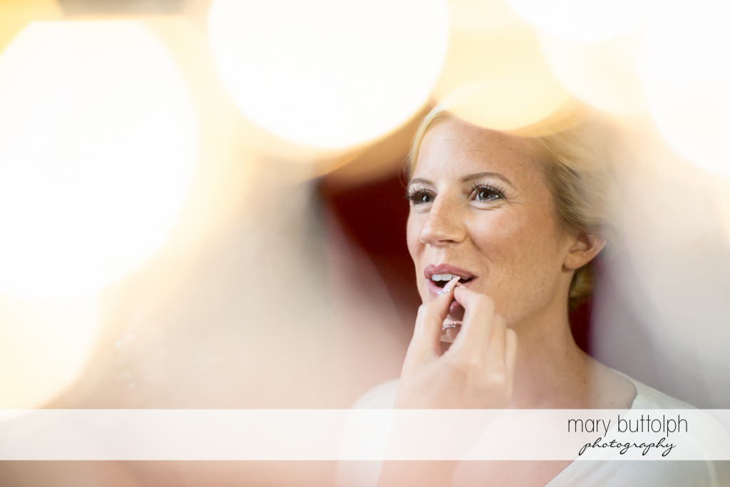 Bride puts something on her lips at Skaneateles Country Club Wedding