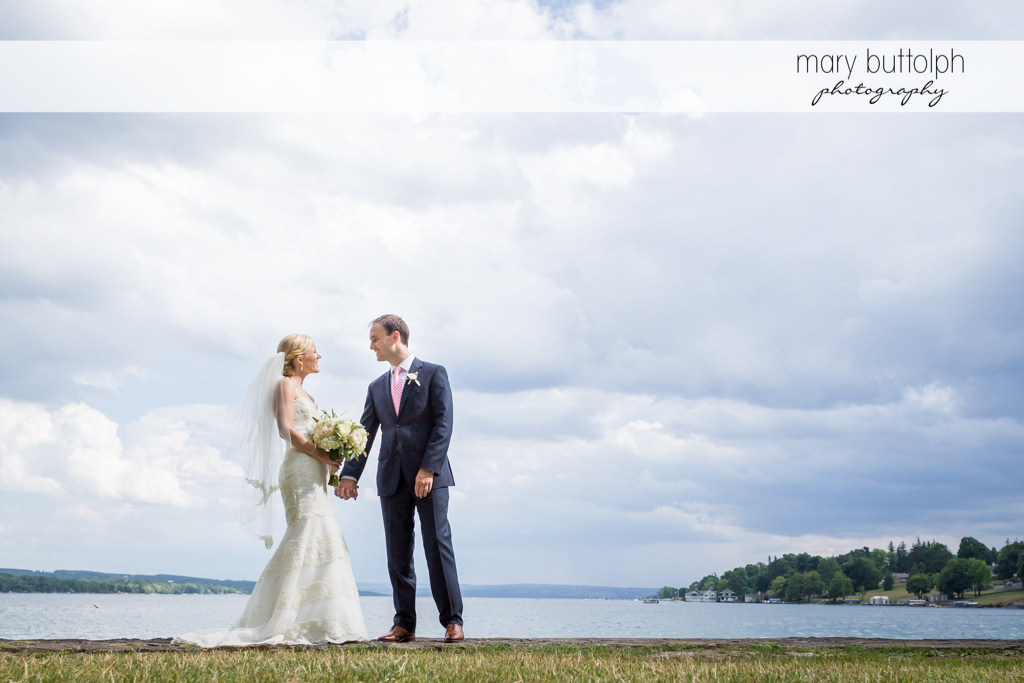 Couple hold hands by the lake at Skaneateles Country Club Wedding