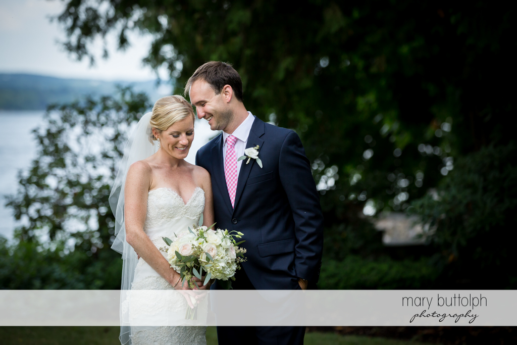 Couple share a tender moment at the garden near the lake at Skaneateles Country Club Wedding