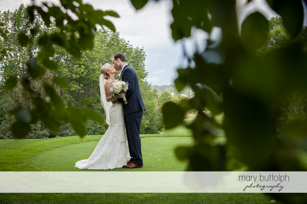 Couple show their love in the garden at Skaneateles Country Club Wedding