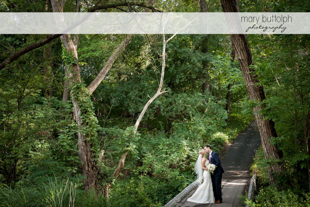 Couple kiss in the woods at Skaneateles Country Club Wedding