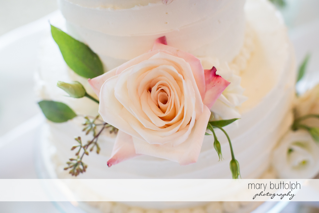 Close up of rose in couple's wedding cake at Skaneateles Country Club Wedding