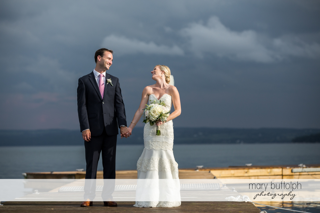 Couple pose by the lake under a dark sky at Skaneateles Country Club Wedding