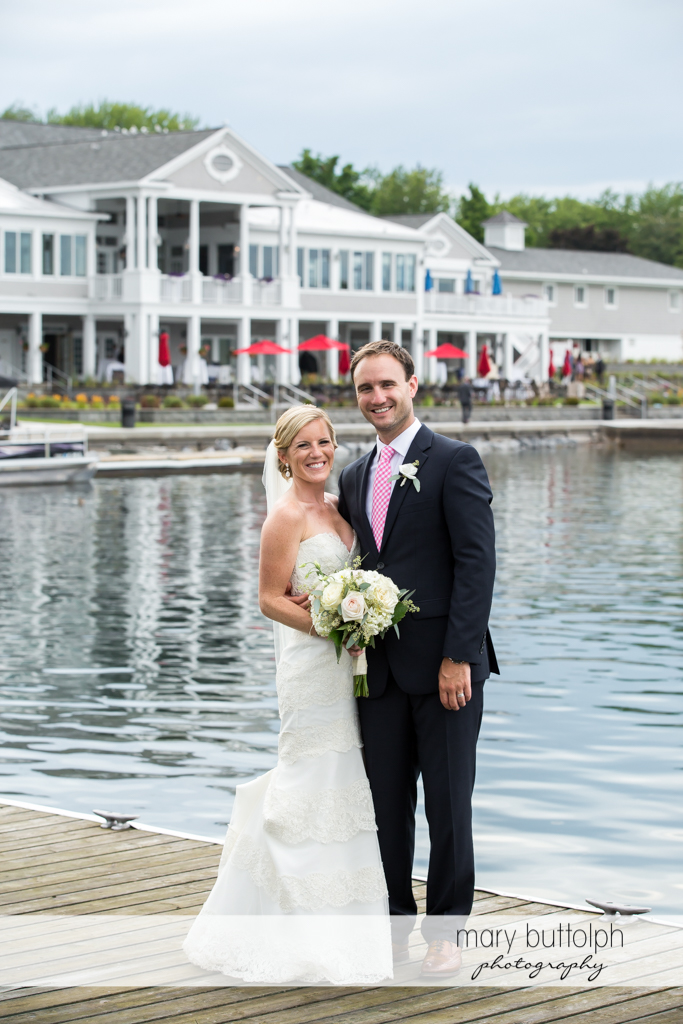 Couple in high spirits by the lake in front of the wedding venue at Skaneateles Country Club Wedding