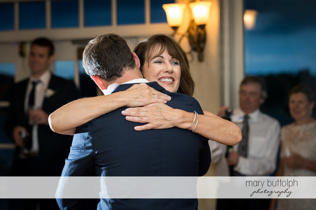 Guests embrace at the wedding reception at Skaneateles Country Club Wedding