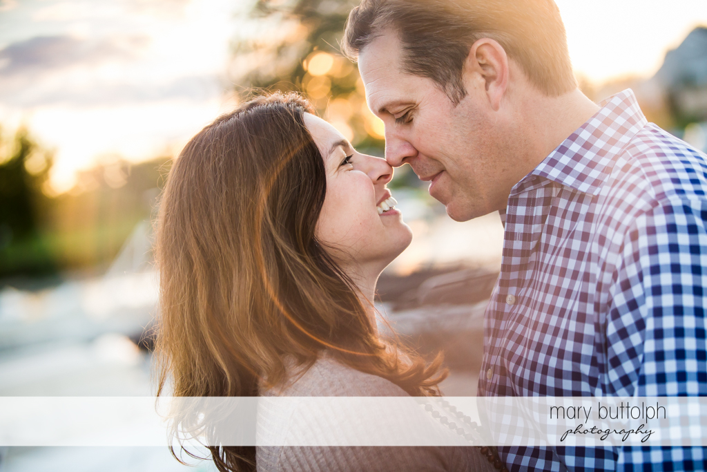 Couple rub noses near the lake at Skaneateles Country Club