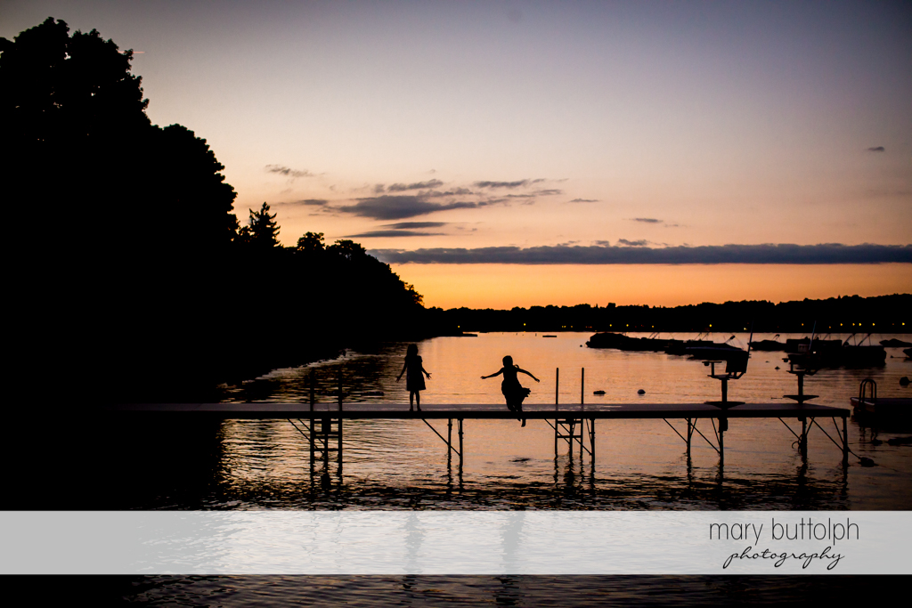 Girls play on the dockas the sun sets at Skaneateles Country Club