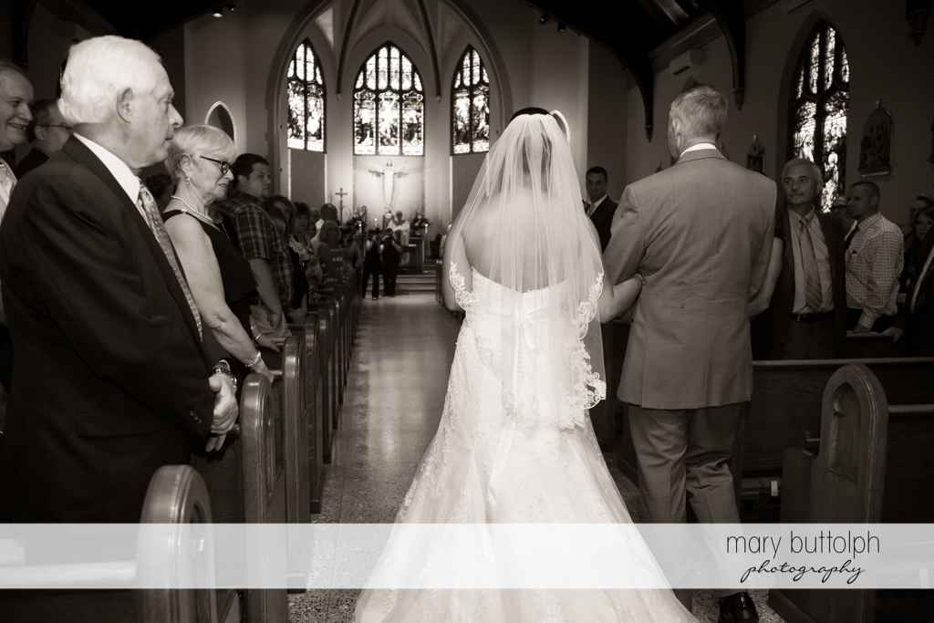 Bride and her father walk down the church aisle as guests look on at The Lodge at Welch Allyn Wedding