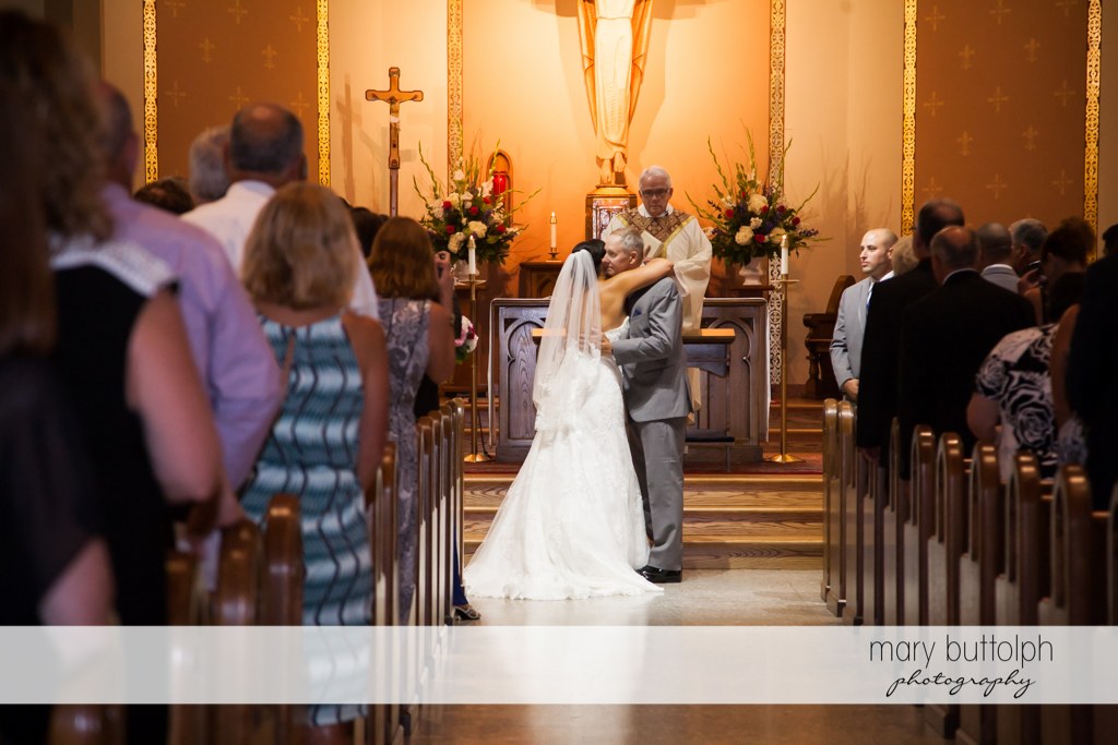 Bride hugs her dad in front of the altar at The Lodge at Welch Allyn Wedding