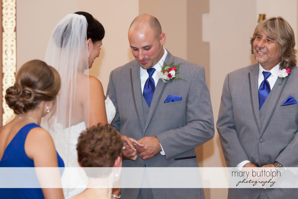 Groom puts the ring on bride's finger at The Lodge at Welch Allyn Wedding