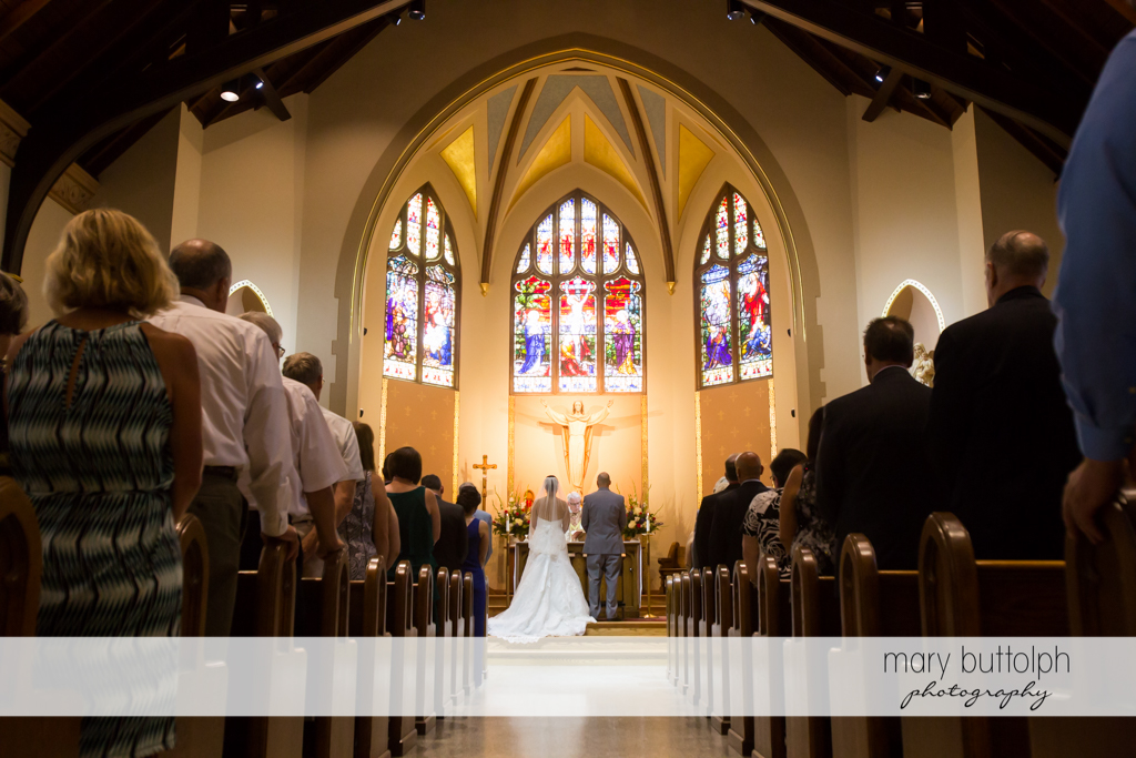 Couple face the altar as guests watch at The Lodge at Welch Allyn Wedding