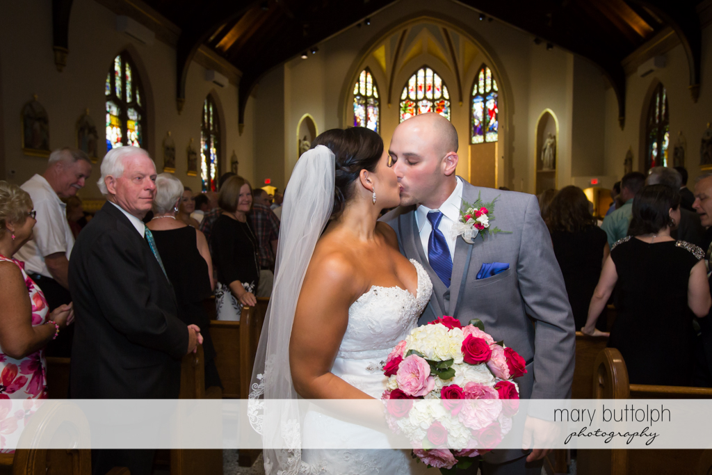 Couple kiss as they leave the church at The Lodge at Welch Allyn Wedding