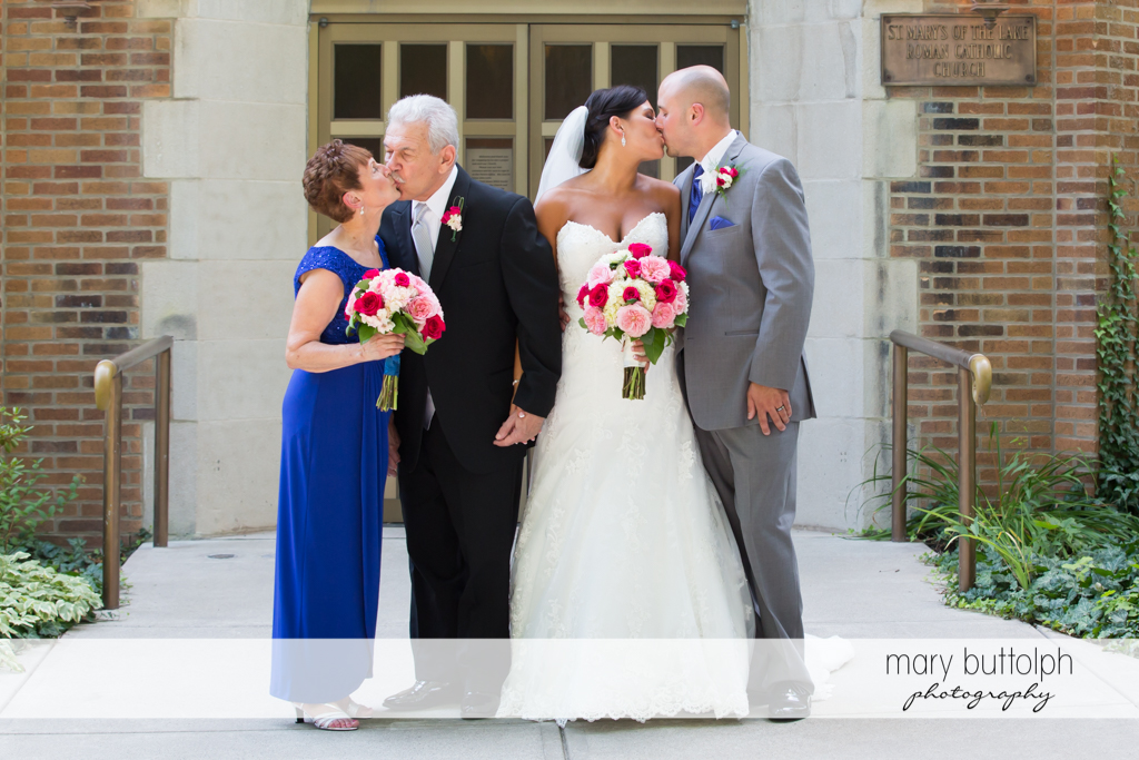 Couple and bride's grandparents kiss in front of the church at The Lodge at Welch Allyn Wedding