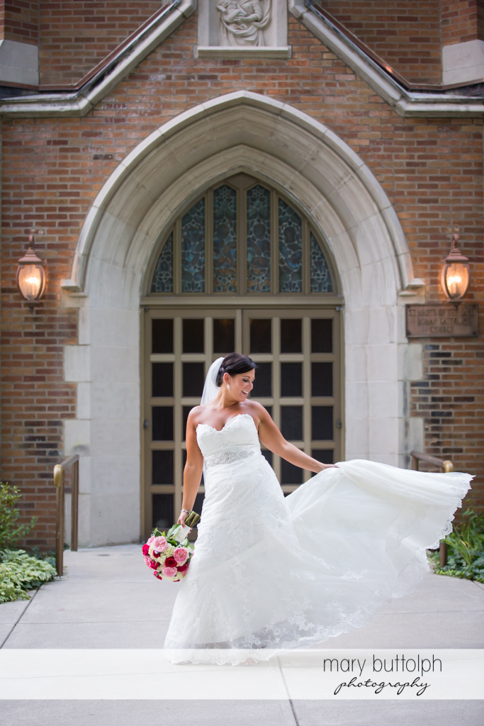 Bride shows off her wedding dress in front of the church at The Lodge at Welch Allyn Wedding