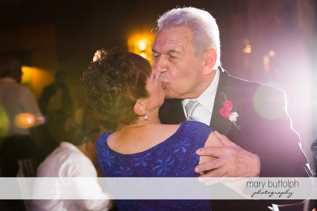 Bride's grandparents kiss at the wedding reception at The Lodge at Welch Allyn Wedding