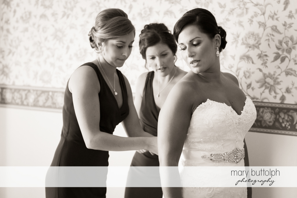 Bride gets help from bridesmaids in putting on her dress at The Lodge at Allyn Wedding