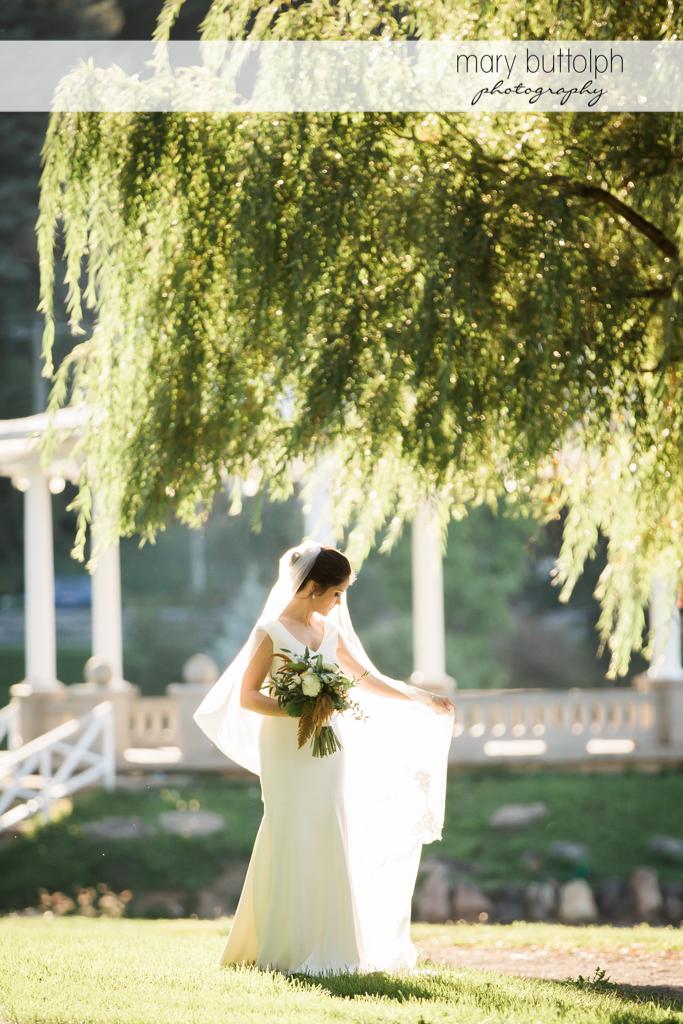 Bride shows off her wedding dress in the garden at Syracuse Wedding