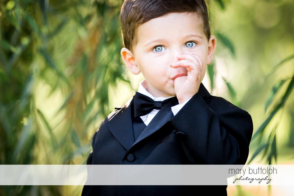 Bride's nephew sucks his thumb in the garden at Syracuse Wedding