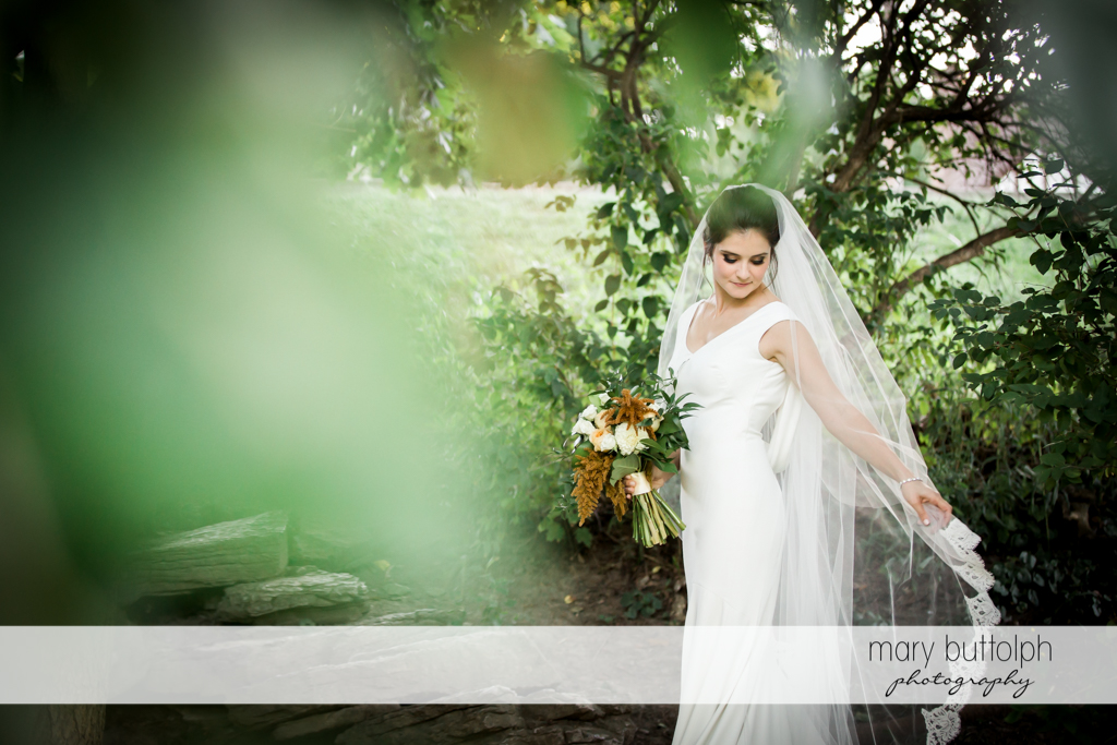 Bride holds flowers in the garden at Syracuse Wedding