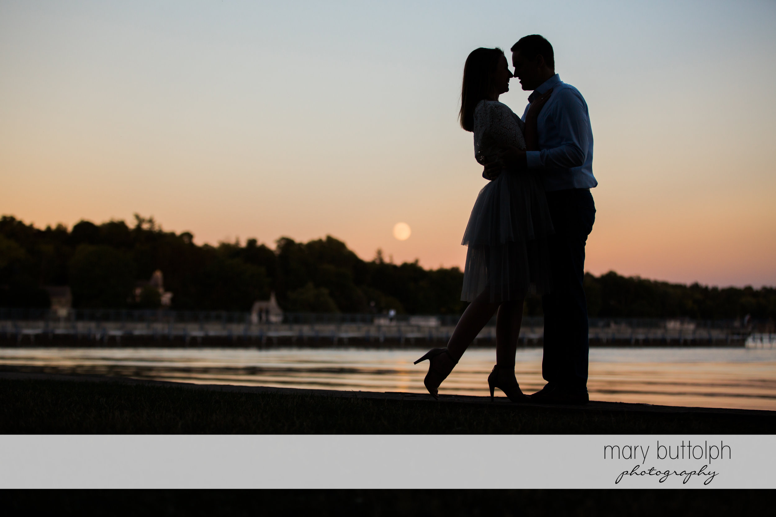 Couple watch the sunset at the lake at Skaneateles Engagement