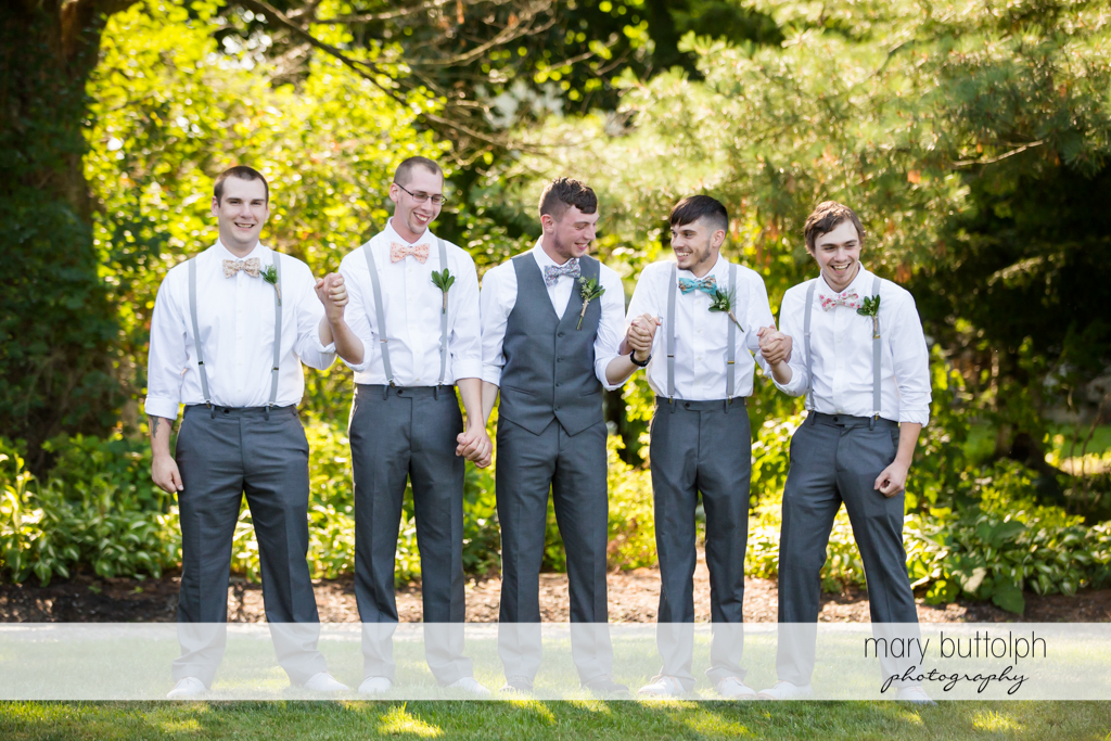 Groom and groomsmen hold hands in the garden at John Joseph Inn and Elizabeth Restaurant Wedding
