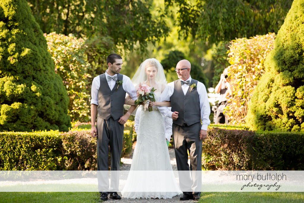 Bride is escorted by her father and a relative in the garden at John Joseph Inn and Elizabeth Restaurant Wedding