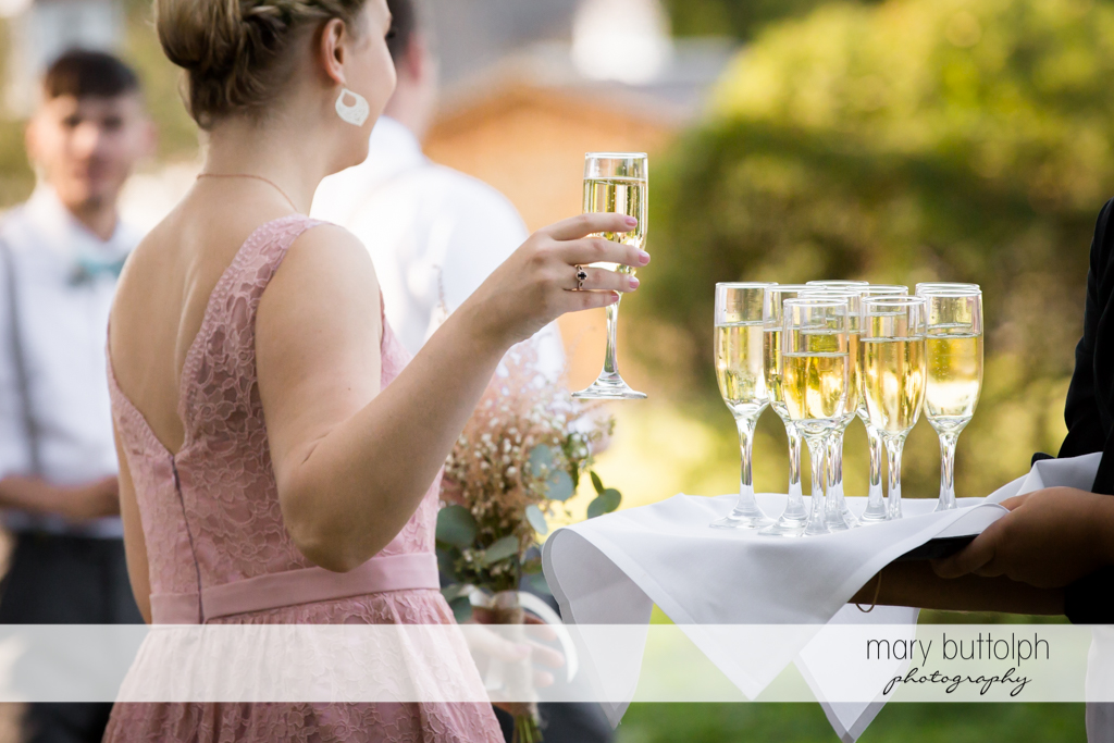 Guest takes a glass of wine at the garden wedding at John Joseph Inn and Elizabeth Restaurant Wedding