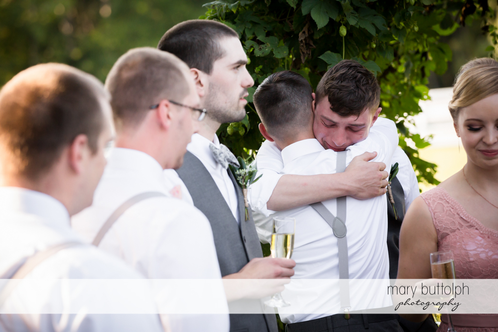 Groom cries as he hugs one of the groomsmen at John Joseph Inn and Elizabeth Restaurant Wedding