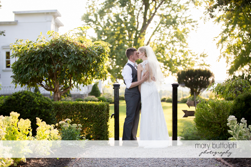 Couple kiss in the garden at John Joseph Inn and Elizabeth Restaurant Wedding