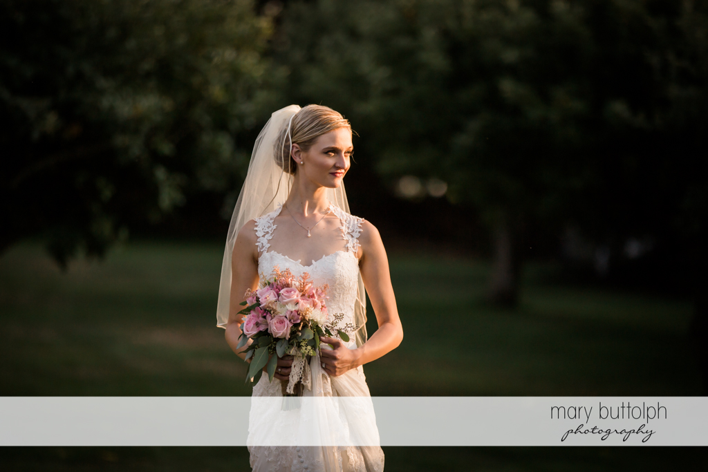 Bride with flowers in the garden at John Joseph Inn and Elizabeth Restaurant Wedding