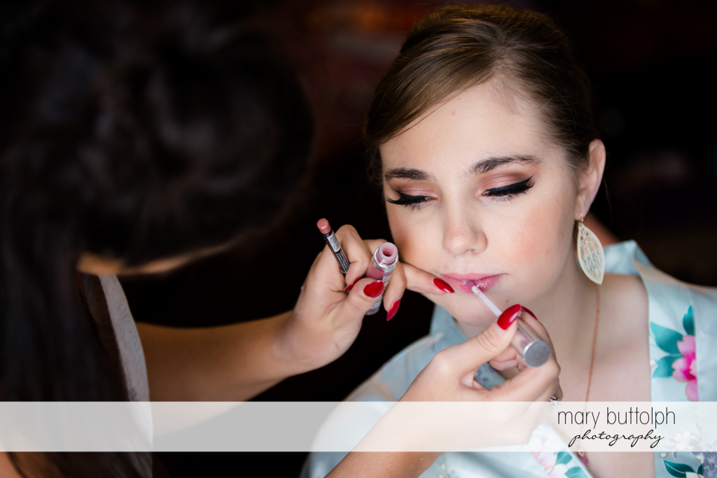 Makeup artist applies lip gloss to a bridesmaid at John Joseph Inn and Elizabeth Restaurant Wedding