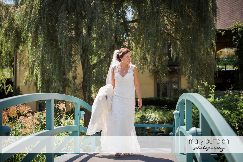 Bride crosses the bridge at The Lodge at Welch Allyn Wedding