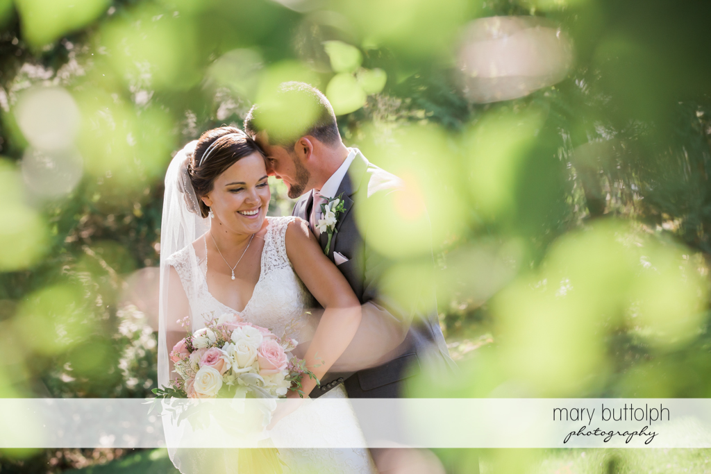 Couple in the garden with flowers in the foreground at The Lodge at Welch Allyn Wedding