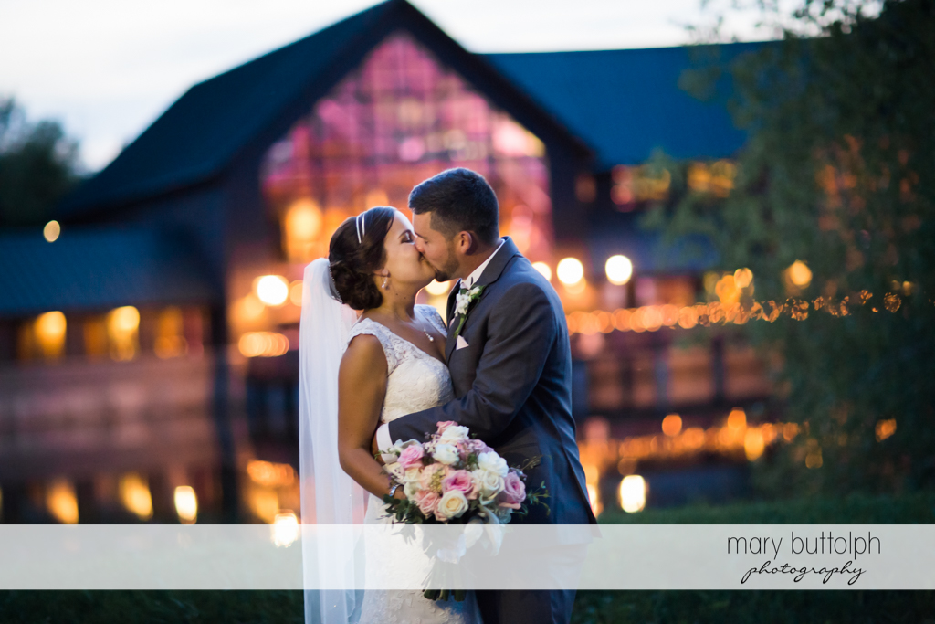 Couple kiss in front of the wedding venue at The Lodge at Welch Allyn Wedding