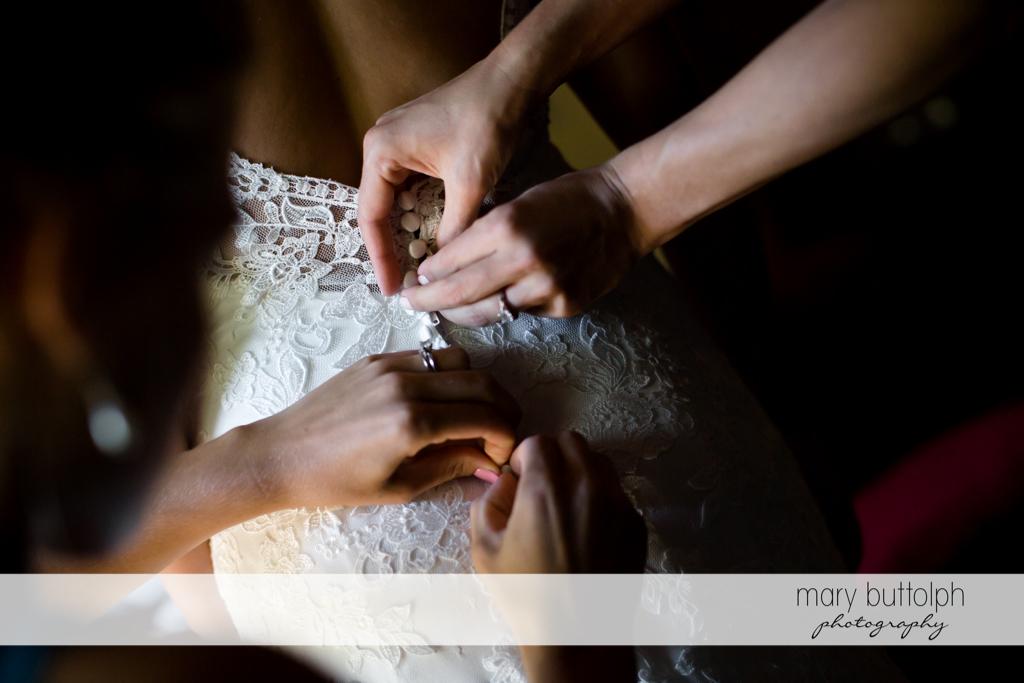 Bride gets help in putting on her wedding dress at The Lodge at Welch Allyn Wedding