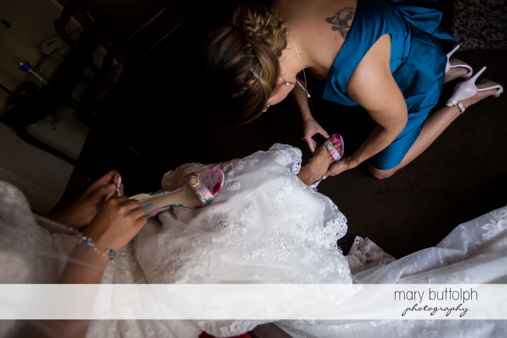Woman helps put on the bride's shoes at The Lodge at Welch Allyn Wedding