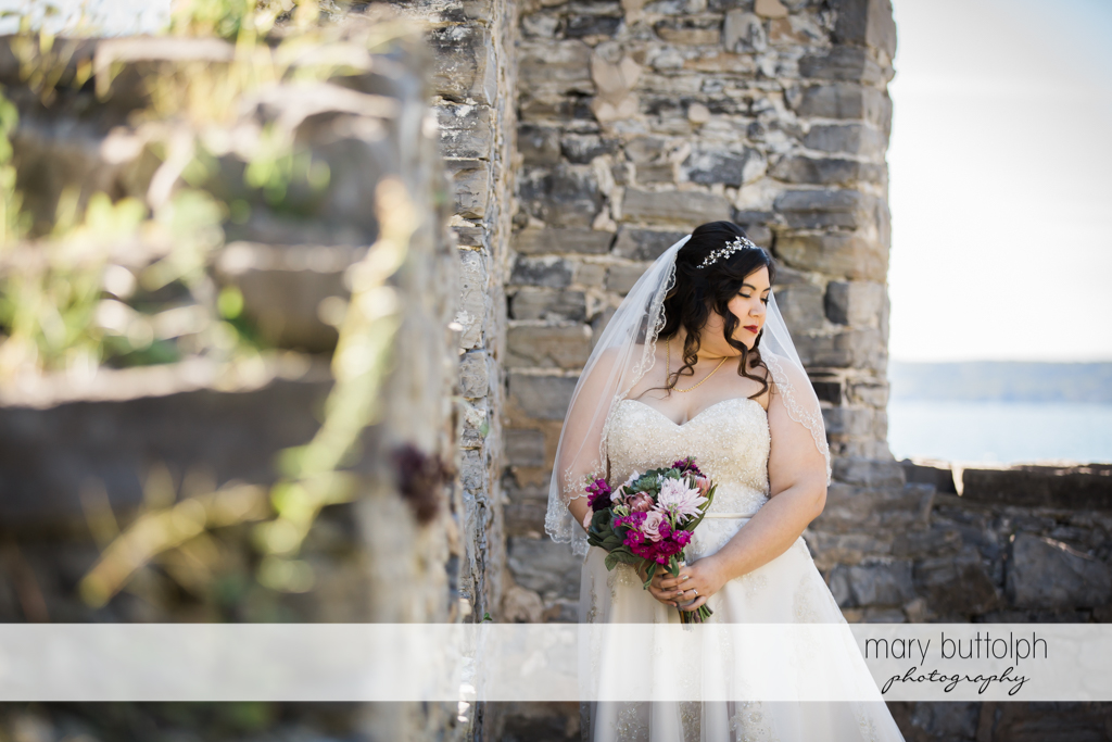 Bride poses with flowers in front of a brick wall at Aurora Inn Wedding