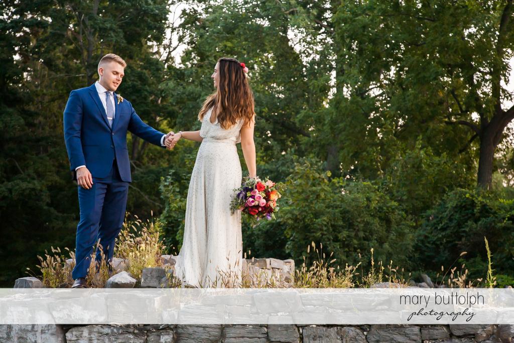 Couple take a stroll in the garden at Aurora Inn Wedding